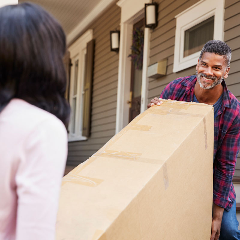 A couple moves a box into their new home