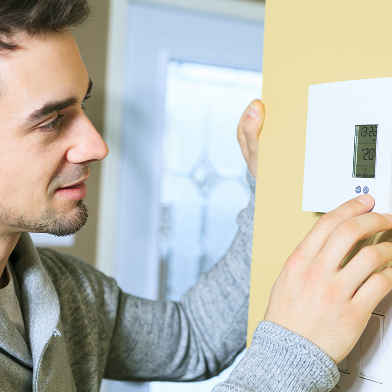 Man checks his home thermometer