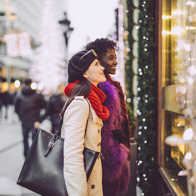 Two women window shop during the holiday season