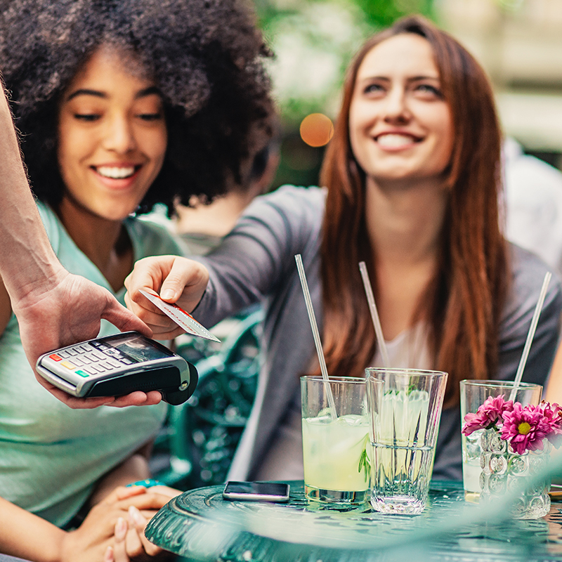 Two women pay for their drinks with a credit card