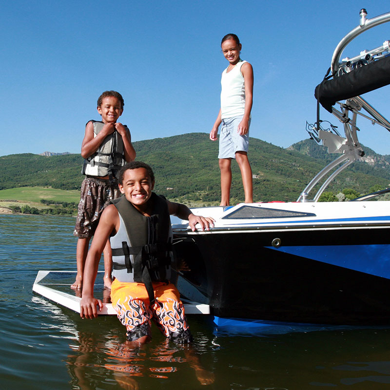 A family spends the day on their boat on a lake
